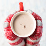 Hands offering hot cocoa