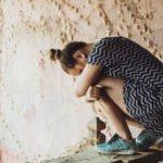 Girl sad alone hugging knees