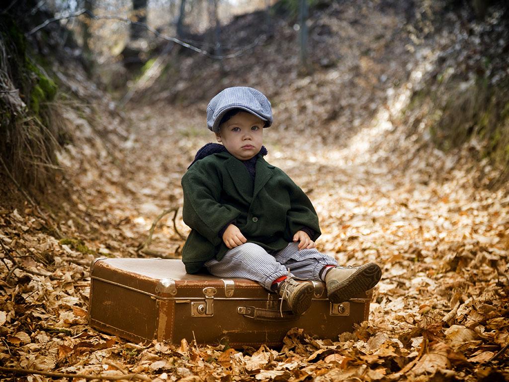 Sad little boy alone in woods