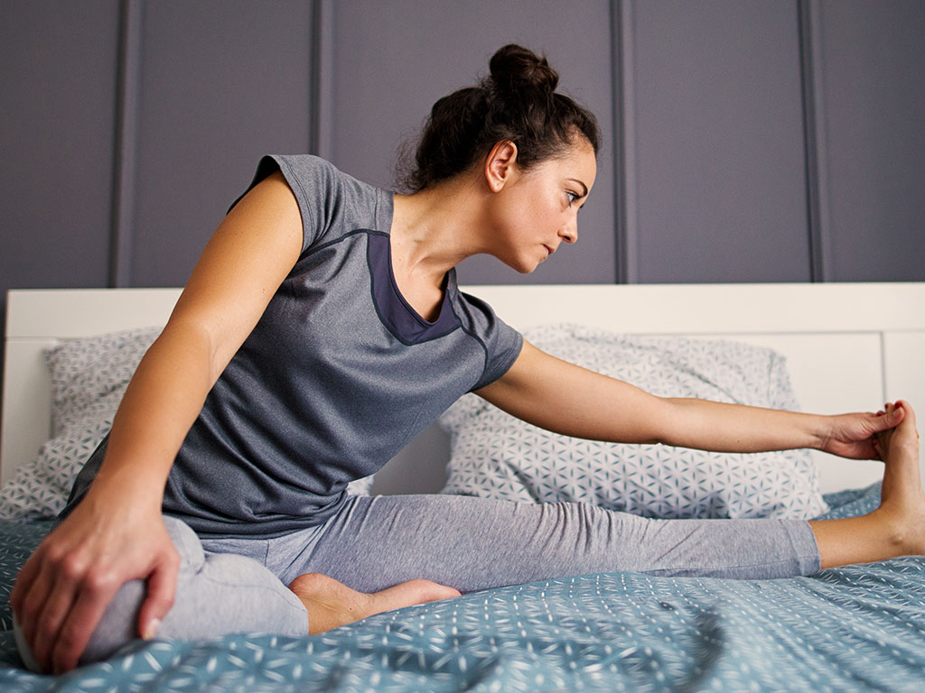 Girl doing yoga in bed