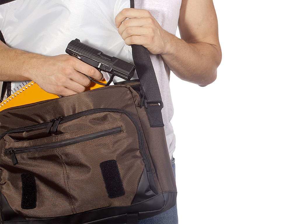 teen putting gun in computer bag