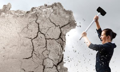 woman chipping away at wall